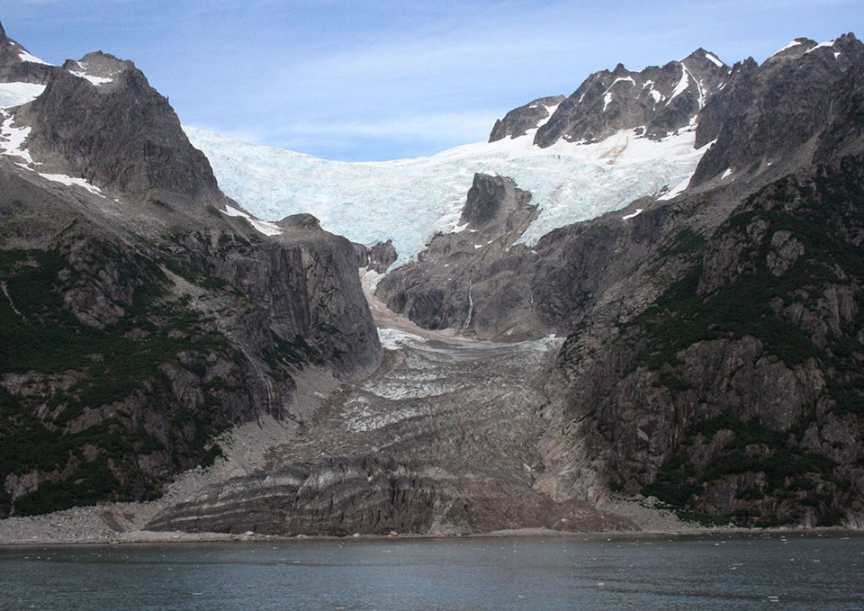 The bottom fifth of the picture is water.  A glacier flows over a mountainside near the top of the picture, and it flows down to the water.  The glacier is white at the top of the image, and brown near the bottom.  It is smaller than the previous image
