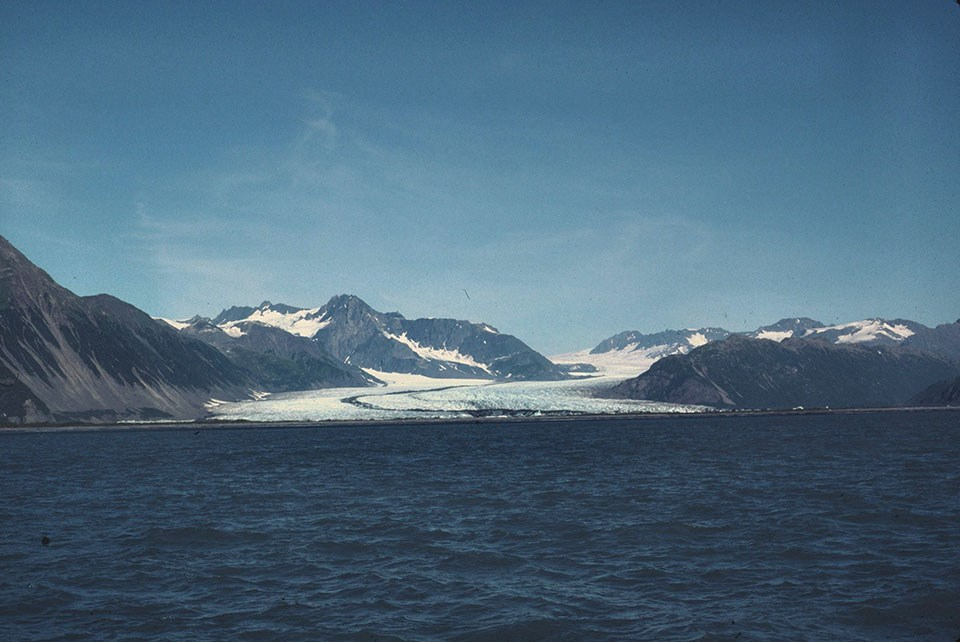 A glacier flowing between mountains down to the ocean.  There is a dark stripe running down the center of the glacier.