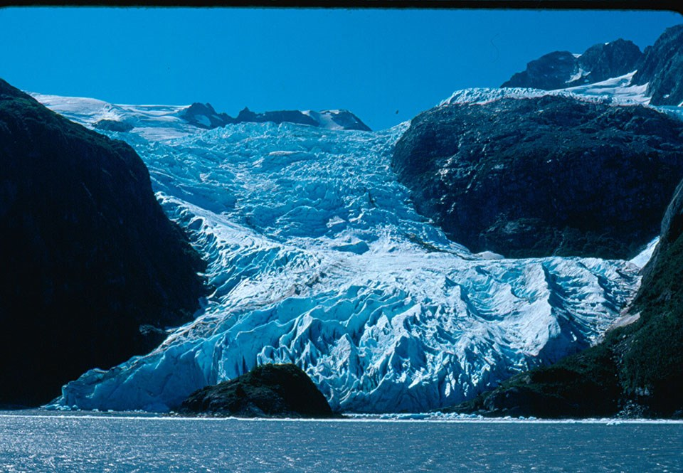 A blue colored glacier flows over a mountainside and down to the water.  There are rocks and land in the water in front of the glacier