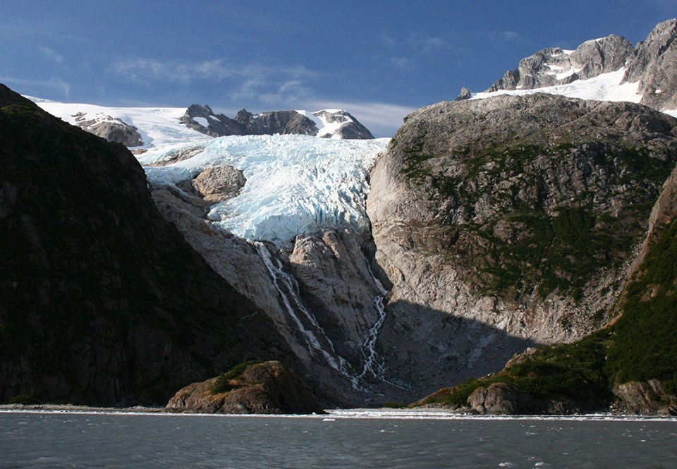A glacier flows over the mountains.  It stops halfway between the top of the mountainside and the bottom.  Some streams flow down the the water from the end of the glacier.