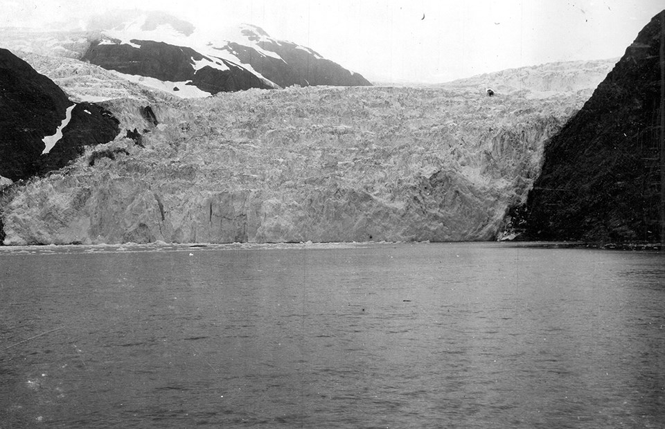 A black and white photo.  The bottom half of the picture is water.  There are mountainsides on the right and left of the picture.  In the middle is a large glacier that meets the water.