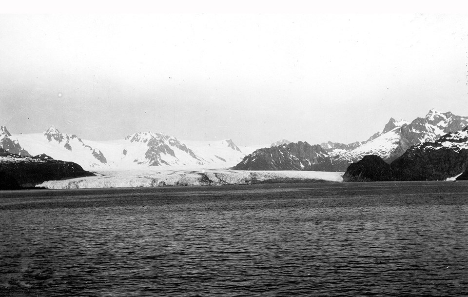 A black and white photo.  The bottom half of the picture is water. In the center of the image is a glacier.  On the left and right of hte glacier are rocky outcroppings.  In the background are snow covered mountains