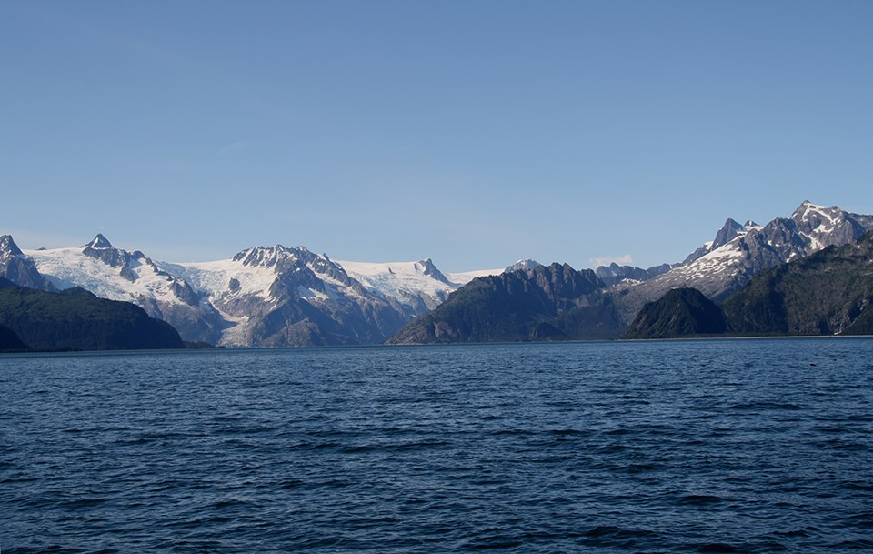 The bottom half of the image is water with small waves.  The top half is mountains.  Some of hte mountains on the left side have snow and ice on them.