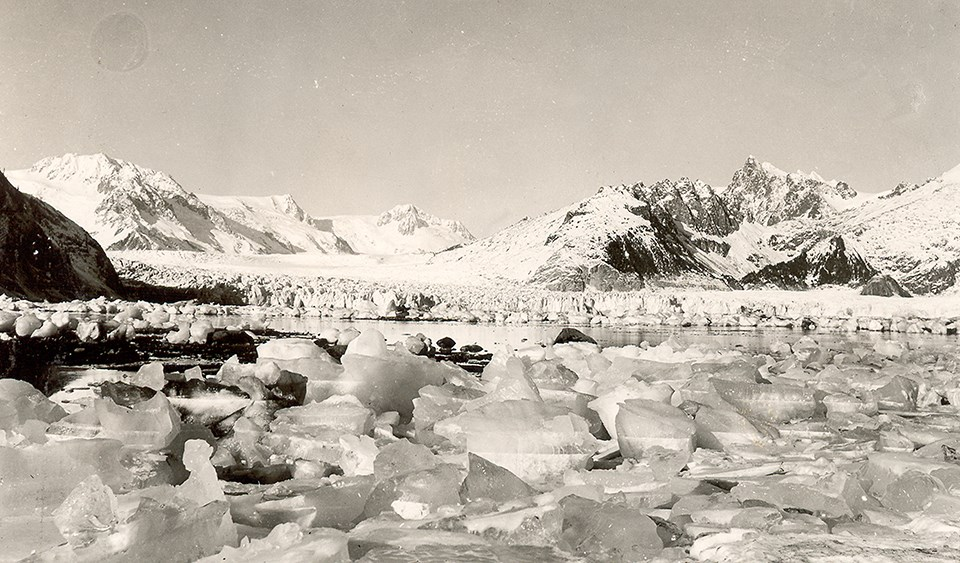 A black and white photo.  Chunks of ice are in the foreground of the image.  BEhind them is a thin strip of water, and then the face of a glacier.  There are snow covered mountains on behind the glacier