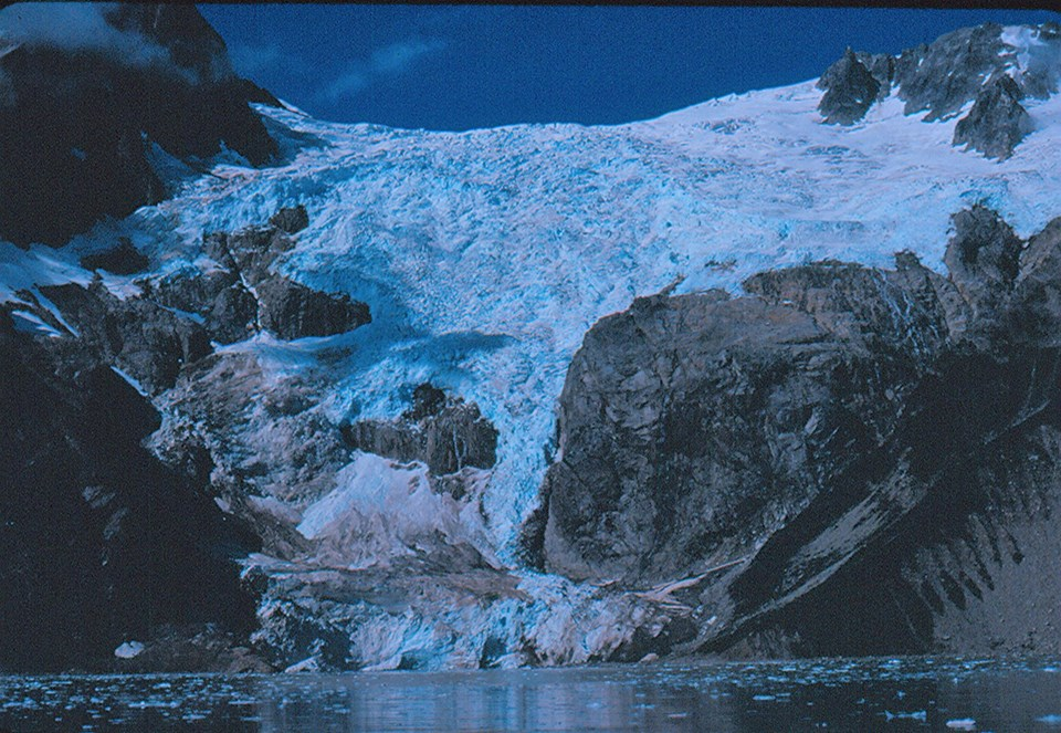 A blue colored glacier flows over a mountainside.  Center right is a large rocky outcropping from undre thglacier.