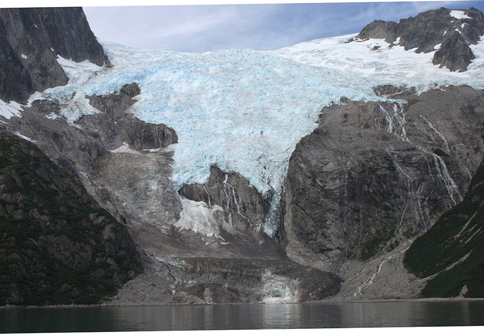 center top of the image a glacier flows over a mountain.  The sides of the image are gray colored rock.  The terminus of hte glacier is covered in dirt and silt.