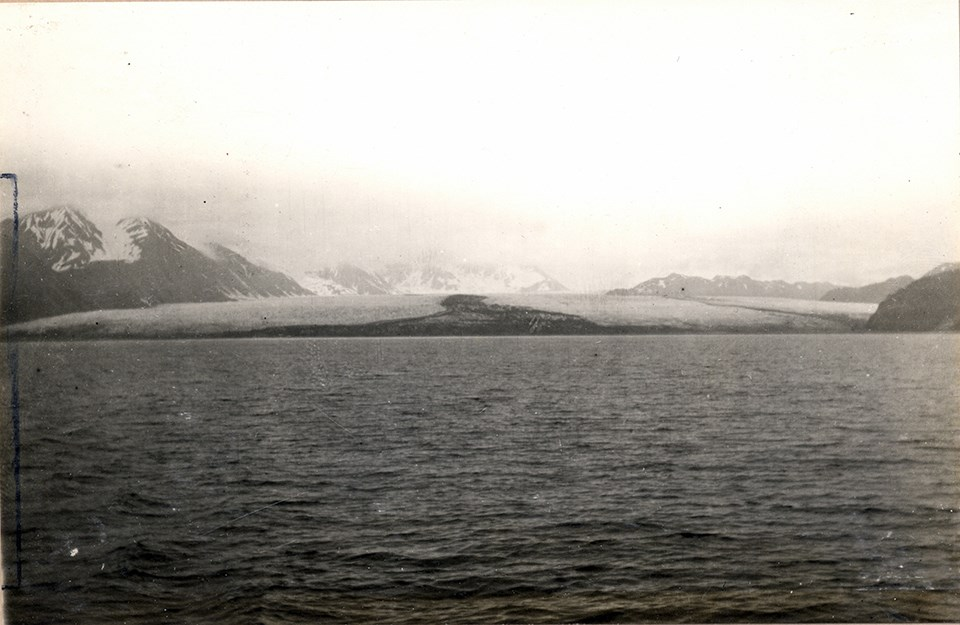 A black and white photo.  The bottom half of the picture is water.  In the top half there is a large glacier in the center of center of the picture.  There are mountains on the right edge and left edge of the picture to the sides of the glacier.