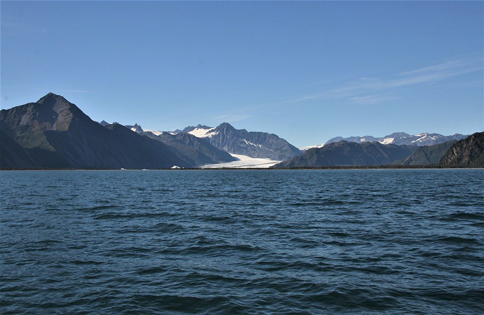 The bottom half of the picture is water.  The top half is mountains in the distance. In the center of the image a small glacier appears between the mountains.