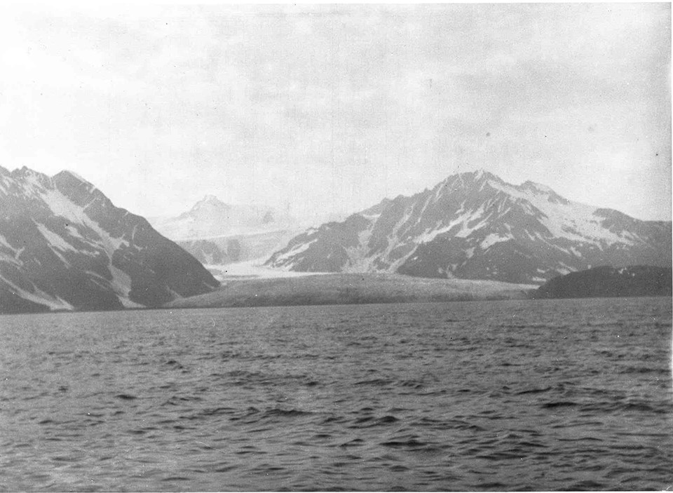 A black and white photo. The bottom half of the picture is water.  Two mountains are on either side of htei mage, and a third mountain is faint in the background.  A white glacier is in the center of the image and comes to the waters edge