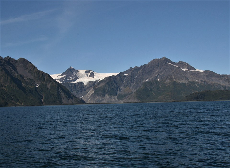 The bottom half of the picture is water.  Three mountains are on the top half of the image above the water.  The third mountain in the background is mostly snow covered except for its peak
