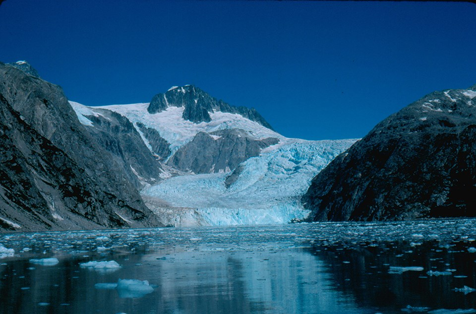 A blueish colored glacier flows from the top center of the image to the bottom center.  Two rocky mountains are on the left of the glacier, and one rounded mountainside is on the right of the glacier.  The bottom third of the image is icy water.