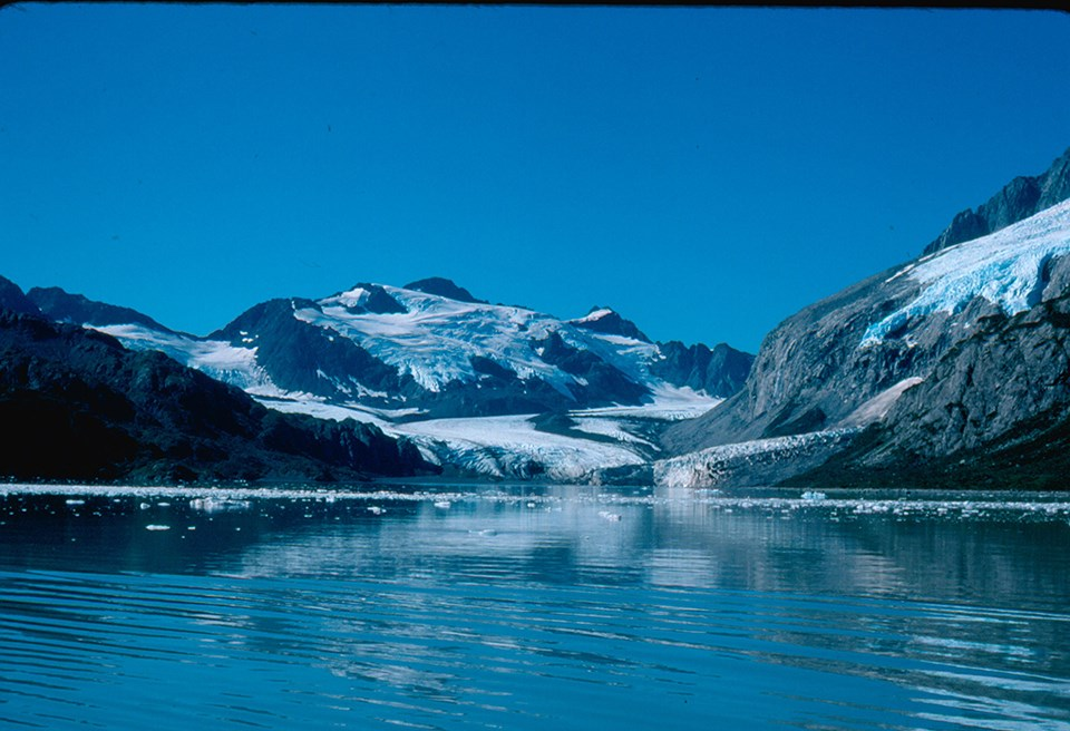 The bottom half of the image is water with chunks of floating ice in it. The top half of the image is mountains with snow patches. In the center of the image a glacier flows from right of center to cent, and down to the water.