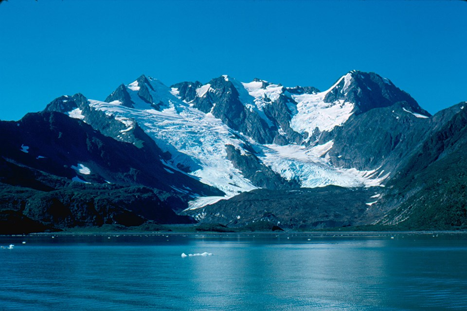 A large mountain is in the center of the image. An alpine glacier flows from the upper left of the mountain down towards the center.  The bottom third of the image is water with ice chunks floating in it.