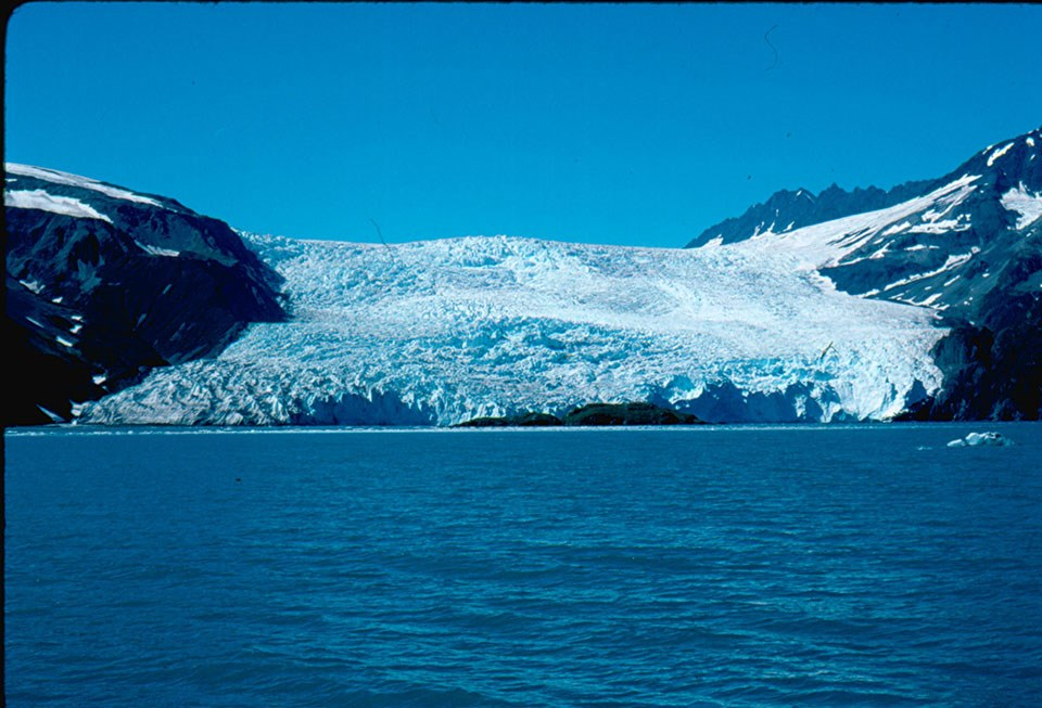 A tidewater in 1990. The glacier is in the center of the image.  The bottom of the glacier is at the edge of water.  the glacier is between two mountainsides