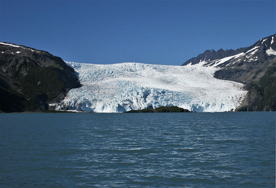 A tidewater glacier is in the center of the image.  The bottom of the glacier is at the edge of water.  the glacier is between two mountainsides