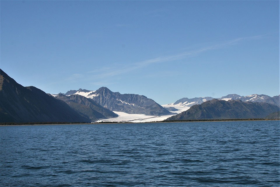 A glacier flowing between mountains down towards the water.  There is a strip of land between the glacier and the water at the bottom of the picture.  The glacier is smaller from the previous picture