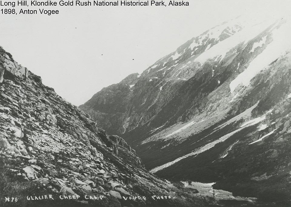 black and white image of rocky mountain with glaciers spilling down a mountain in the background