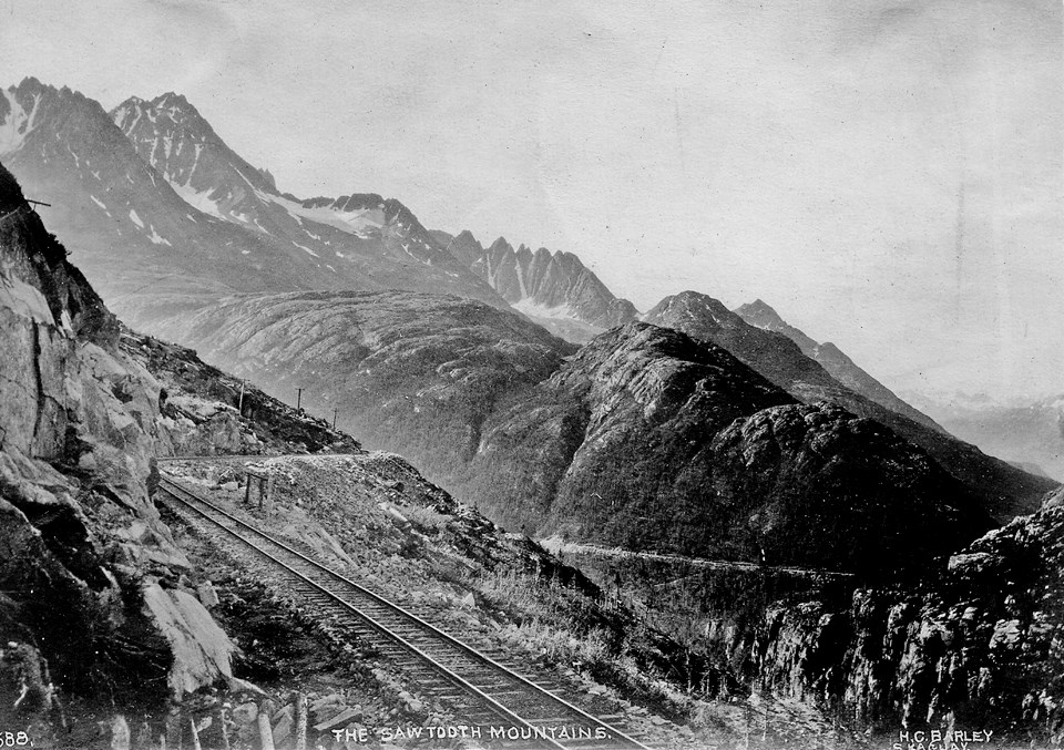 Black and white image of train tracks and mountains