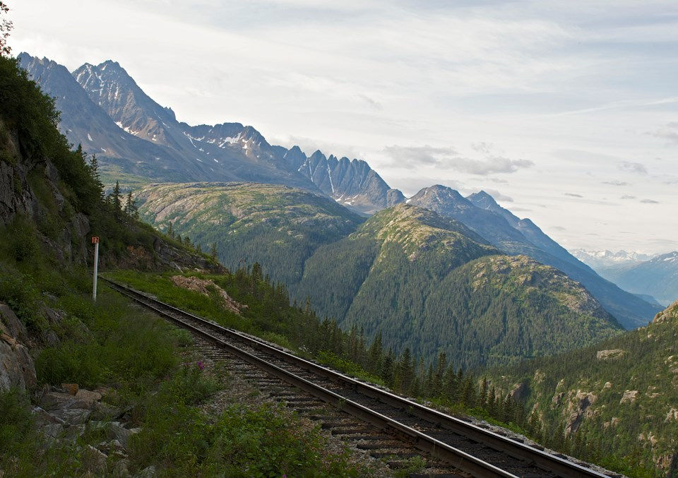 Color image of train tracks and mountains with vegetation along the tracks