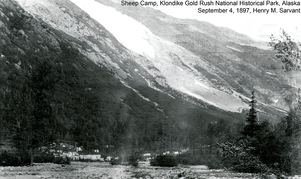 Black and white image of tents and buildings at the base of a mountain with a glacier above it