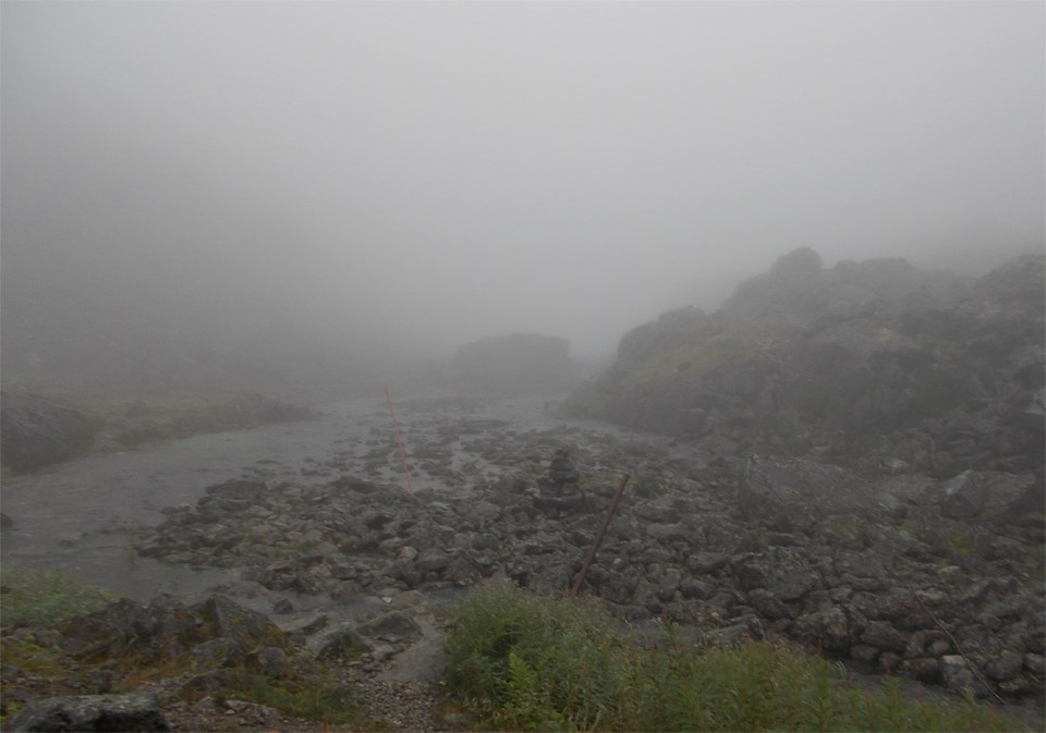 Cloudy view of a rocky area with a stream in the middle and almost no vertical visibility