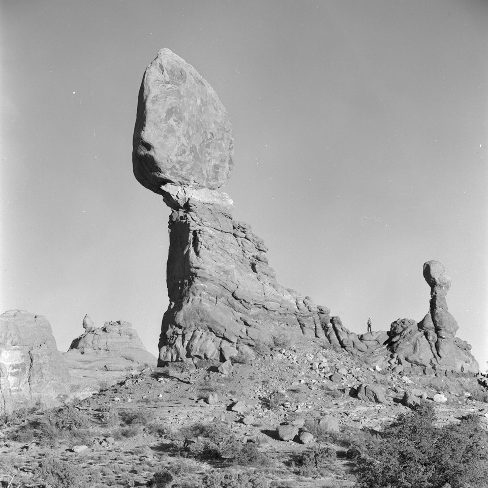 A massive rock perched on a smaller pedestal. A smaller pinnacle stands to the right.