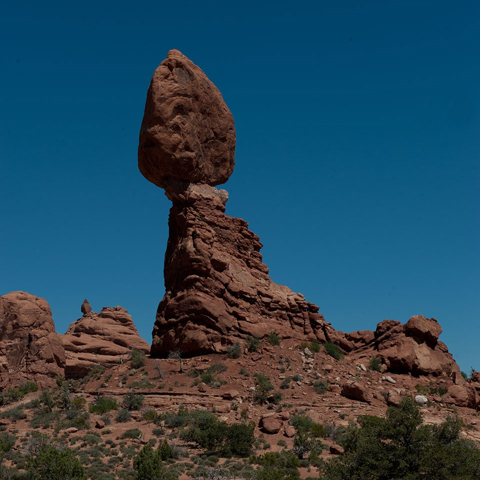 A massive rock perched on a smaller pedestal. The smaller pinnacle to the right is gone.