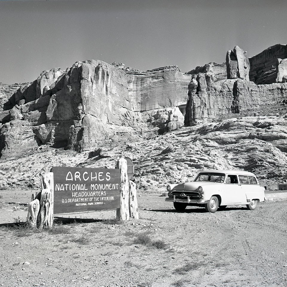 "A black and white photo shows a sign reading ""Arches National Monument"" and a 1950s-era car sit in front of a tall rock wall in the background"