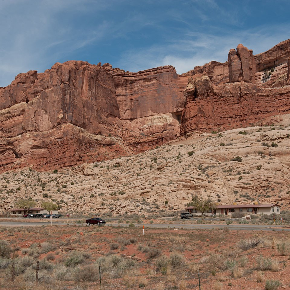 a vehicle drives on a paved road before a tall red rock wall