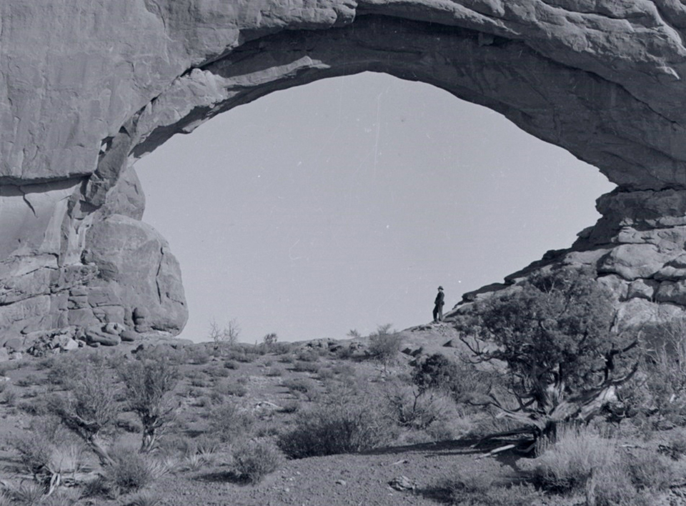 a black and white photo of North Window. A man stands under the arch on the right side. There are plants and soil on the stone below the arch.