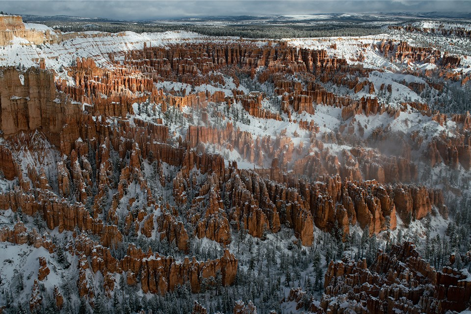 Wintry landscape of red rock spires, cliffs, buttes, and forested plateau