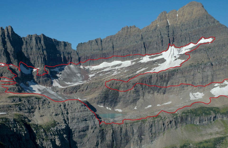 A mountain with some snow and ice. A red line outlines where a glacier used to be.