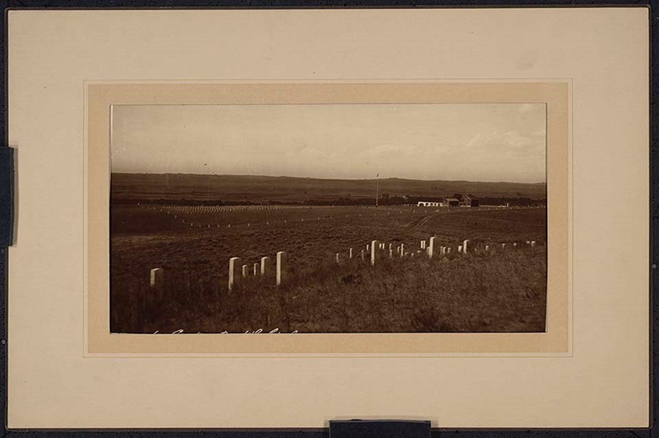 A mounted (purple-brown toned) photograph mounted on card, with embossed mat; Custer group with the National Cemetery and custodian's quarters in backgroun