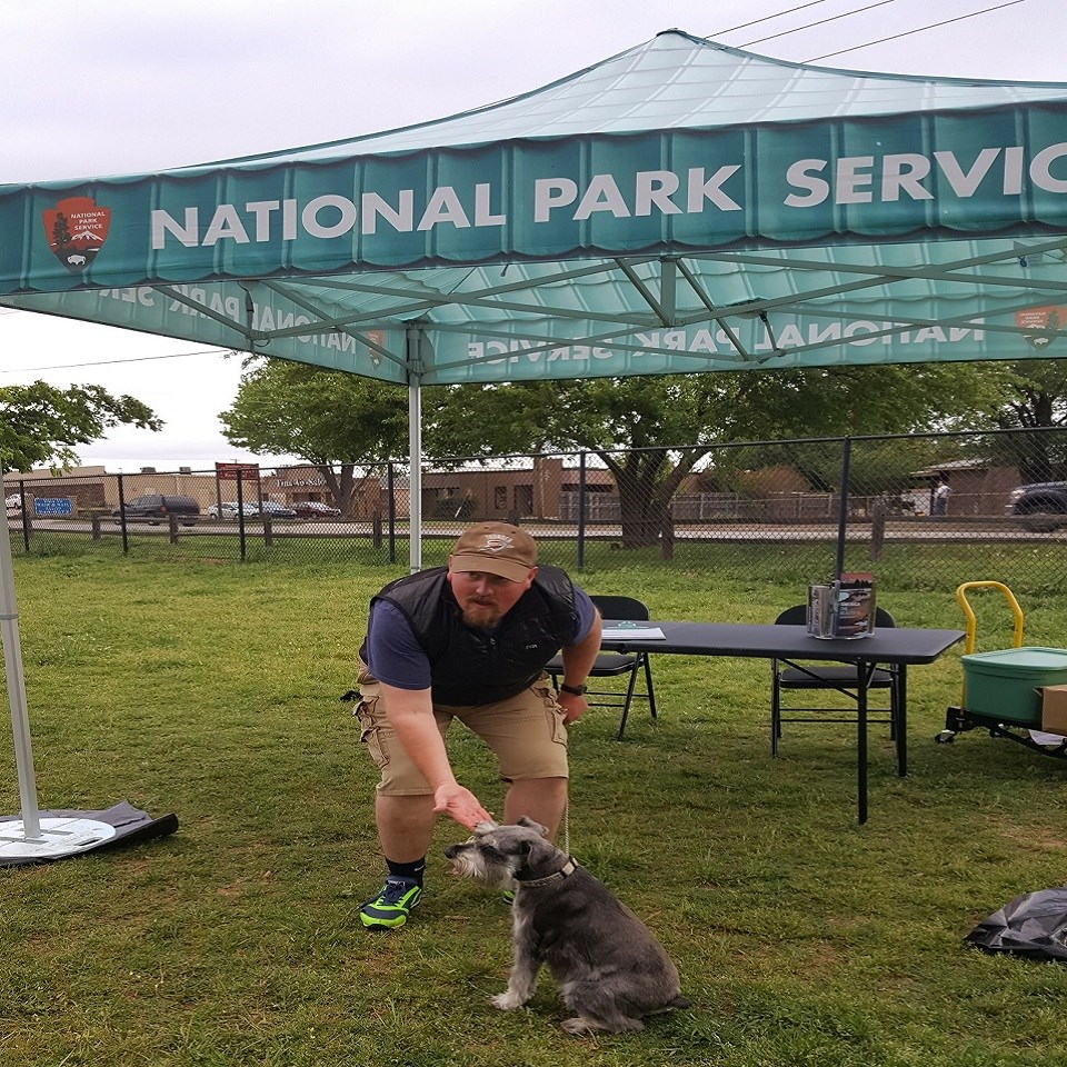A man holding his hand out to a small gray dog in a grassy field under a canopy that says National Park Service across the top.