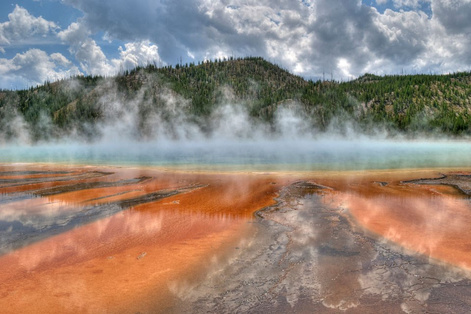 Deep oranges, reds, and browns extend out from a blue pool of steaming water.