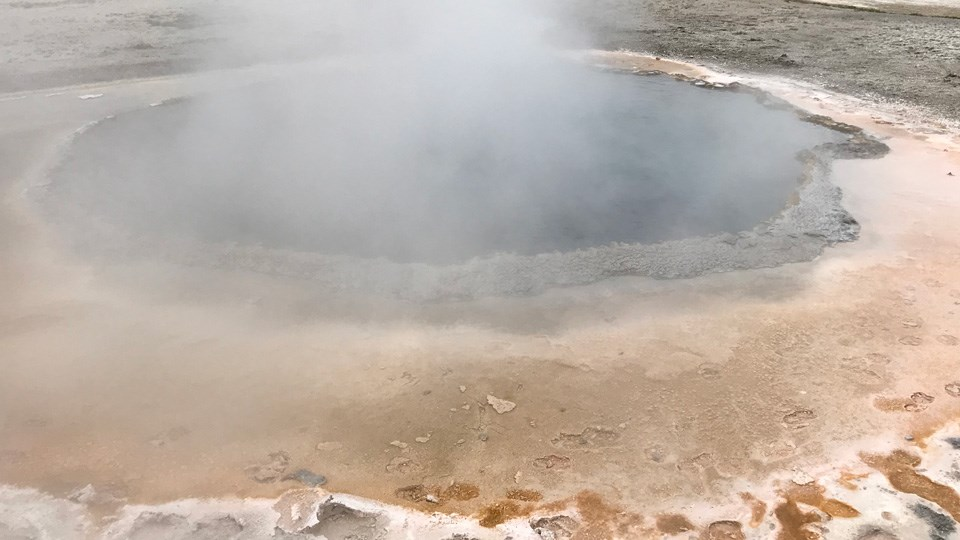 Hot, blue waters of a steaming hot spring, surrounded by the whites and oranges of thermophiles.