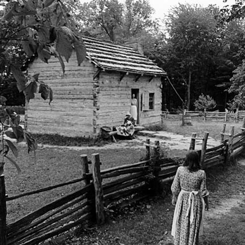 Black and white picture of a log cabin. One woman walking the trail to the cabin, the other at the doorway of the cabin. Split-rail fence in front.