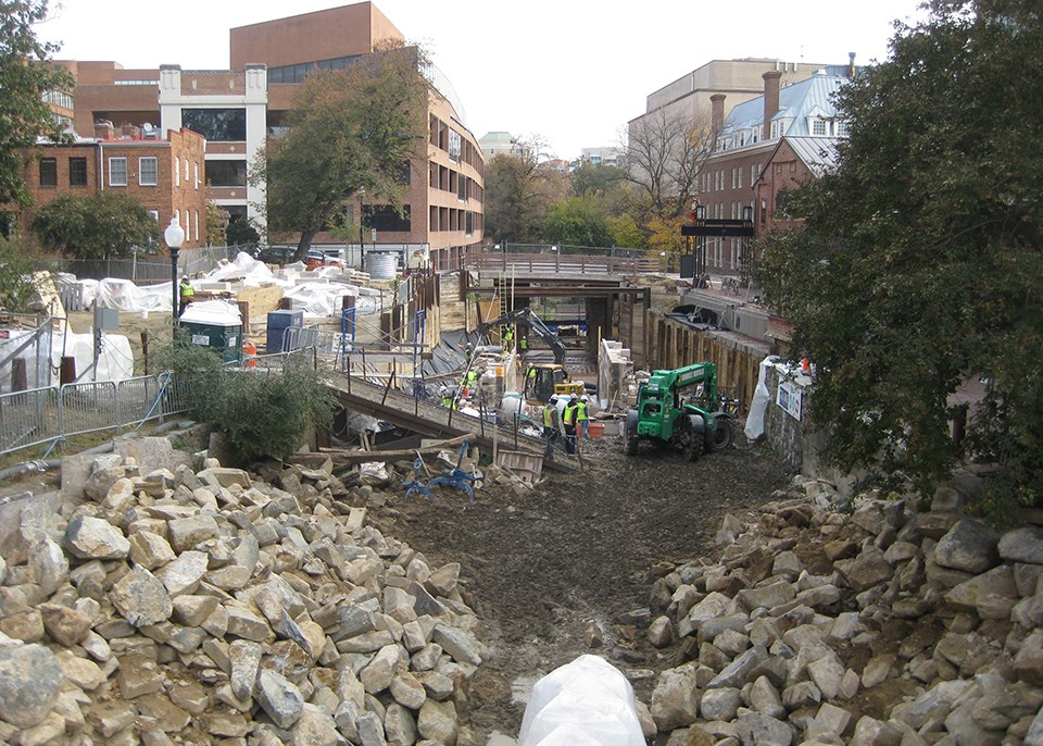 Two parallel light colored cut stone walls under construction.  Construction is down in a excavate surrounded by buildings in an urban setting