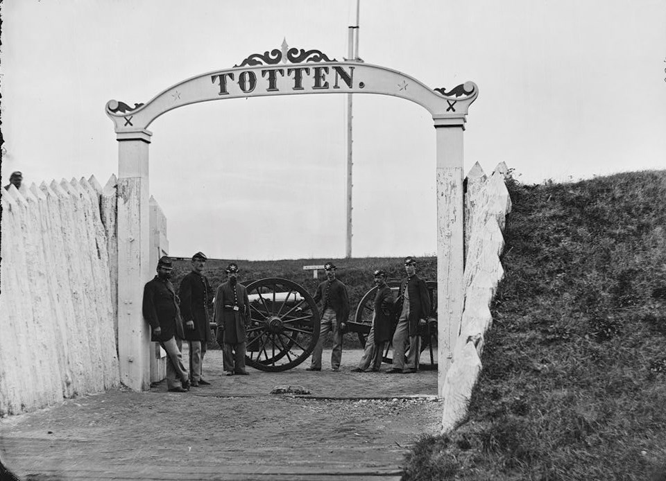 "Union soldiers lean on cannons under an archway that reads ""TOTTEN"""