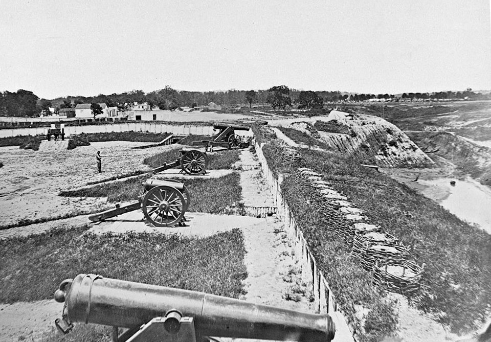 Cannons lined along an embankment in a large, cleared area.