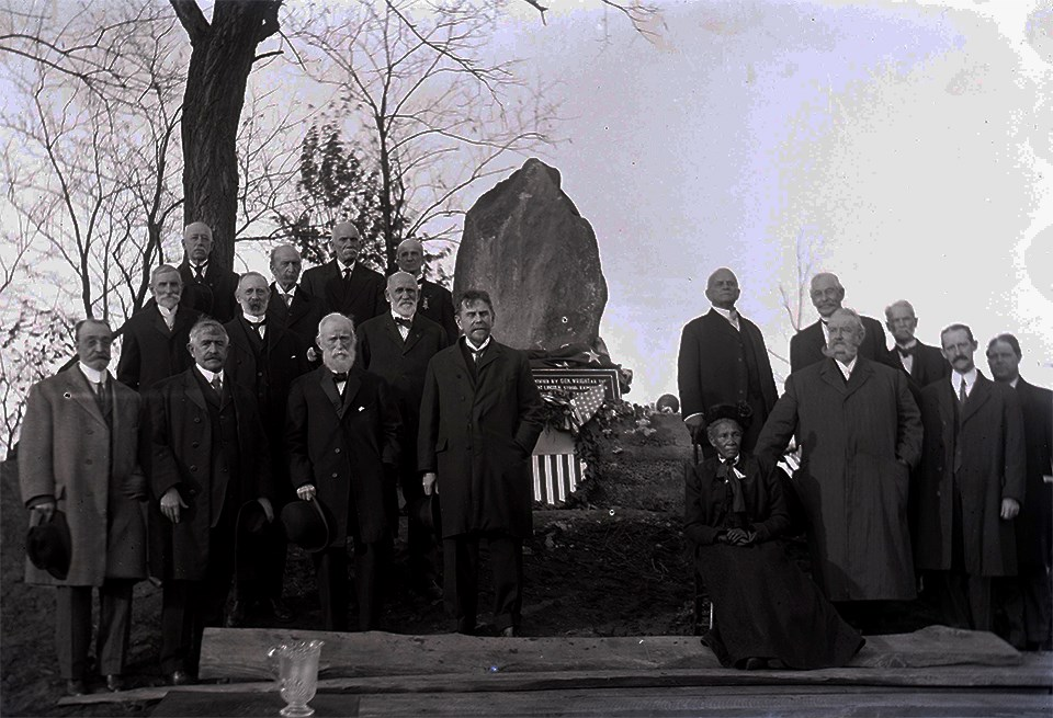 A group of men in dress coats and a seated woman in front of a stone marker