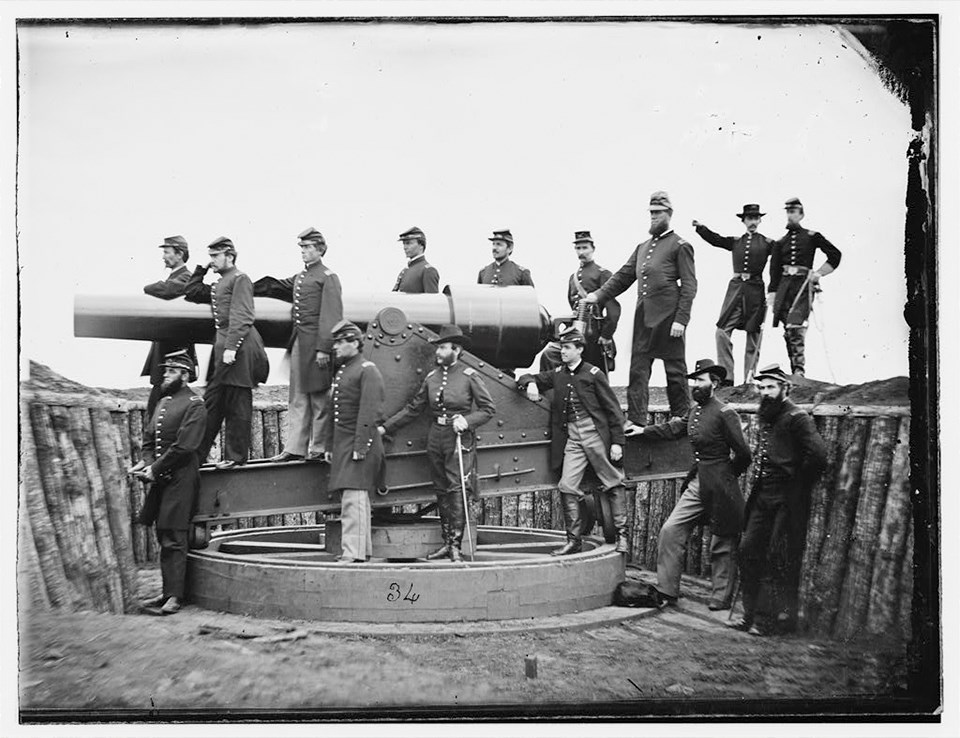 Soldiers pose with a large cannon on a fort wall