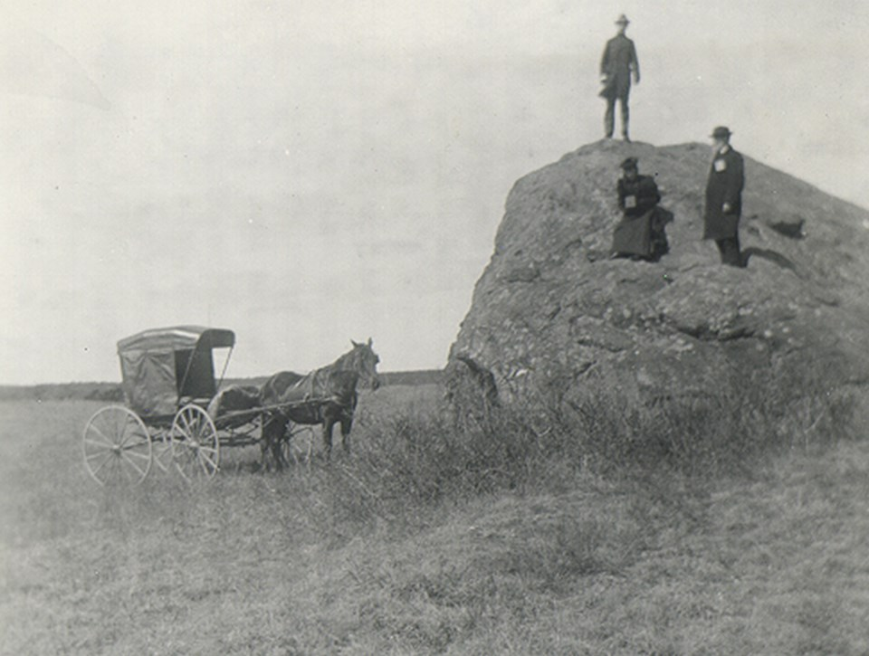 A black and white photo of three people sitting on a large boulder in an open field.