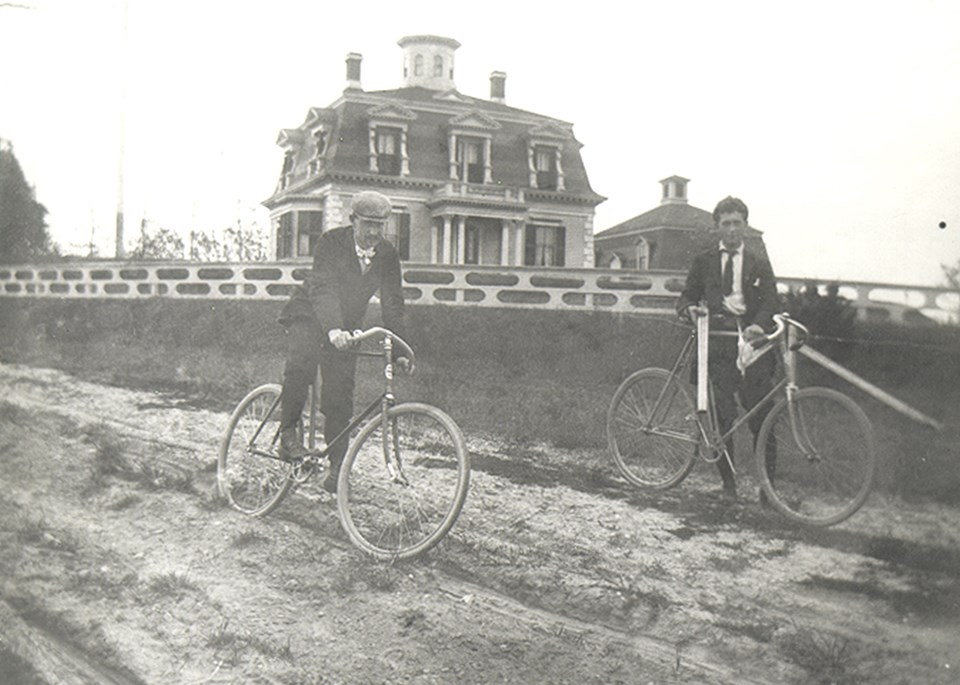 Two men sit on bicycles on a dirt road in front of a large house on a hill.