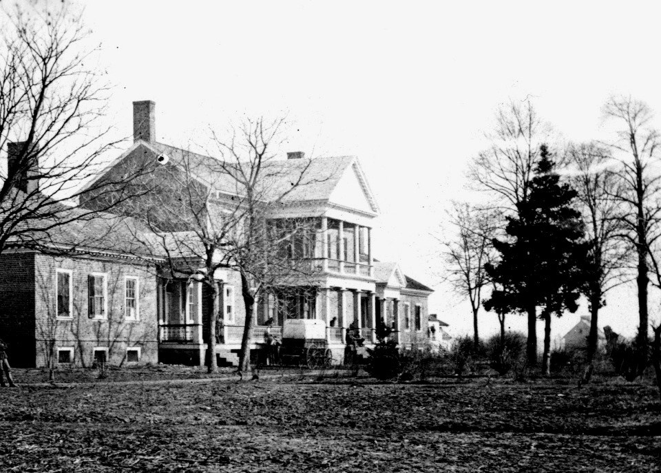 Black and white photo of large brick house with Civil War wagon and a number of trees in front
