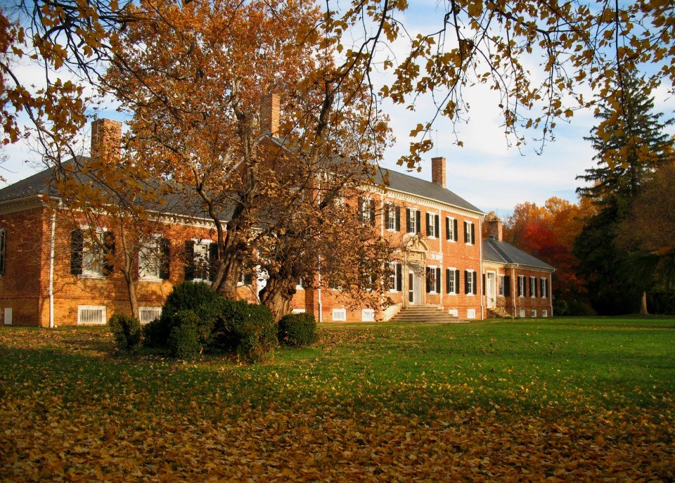 Large brick house with blue sky in background surrounded by trees with fall colors and leaves on ground
