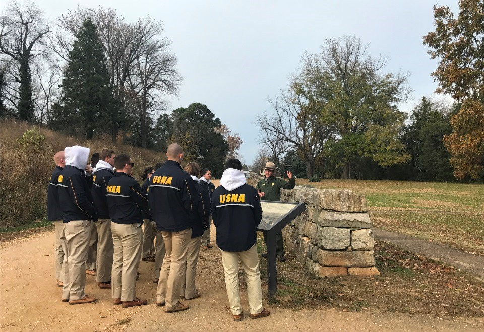Ranger conducts staff ride for navy cadets in blue jackets with stone wall behind him