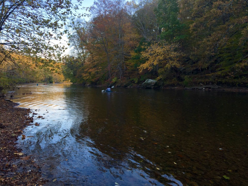 A person in a kayak travels down the Brandywine Creek on a mid fall day.