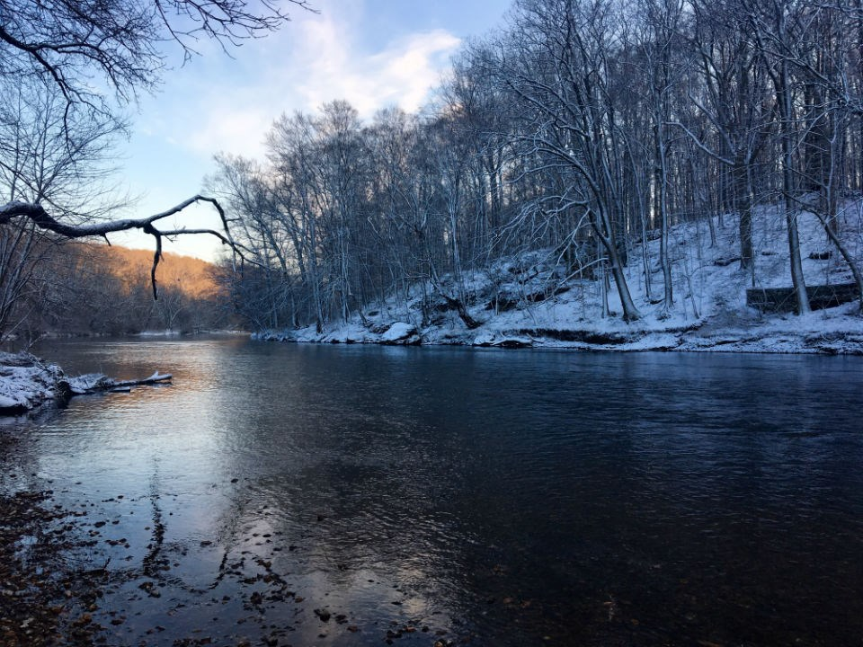 Looking down the Brandywine Creek after a snow fall while the sunsets on the water.