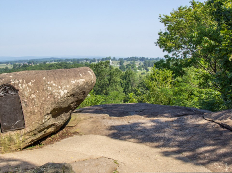 A large boulder on the left overlooks the summit of Little Round Top.